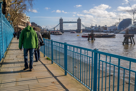 britannia: Tourist Walking along the riverbank of River Thames with the Tower Bridge visible