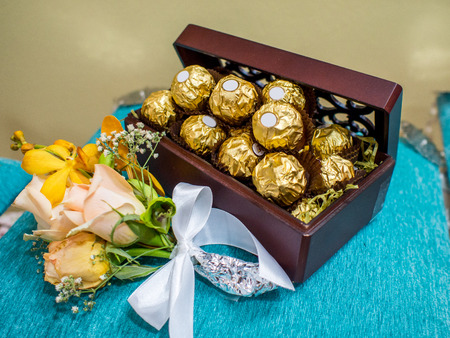 ferrero: Chocolates in Gold Foil in a box on a velvet pillow as a wedding gift Stock Photo
