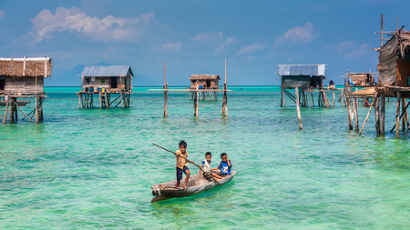 Sea Gypsy Kids on their sampan with their house on stilts in the background 新聞圖片