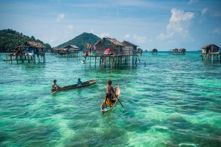 zancos: Sea Gypsy Kids en su champ�n con su casa sobre pilotes en el fondo