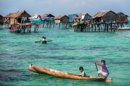 mabul: Sea Gypsy Kids on their sampan with their house on stilts in the background Editorial