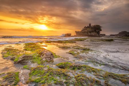 Zonsondergang op het strand vol met groene mos. Tanah Lot Bali.