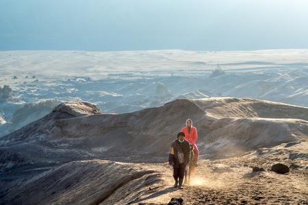 tengger: Tourists Riding Horses up the desert at Bromo Tengger Semeru National Park