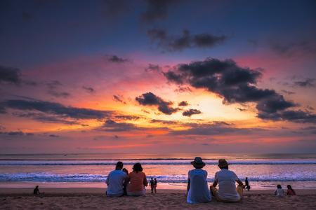 観光客がバリ島クタ ビーチで夕日を表示します。