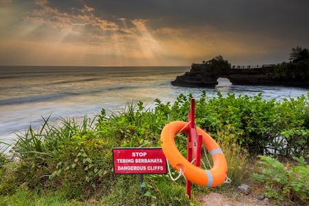 warning lights: Warning Sign at a cliff and ray of lights at pura batu bolong, bali