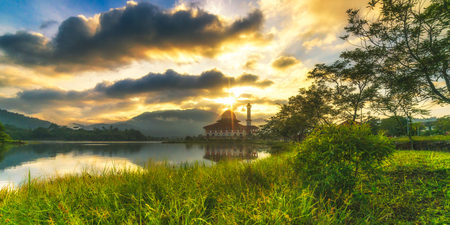 house of worship: Sunrise at a mosque by a lake Stock Photo