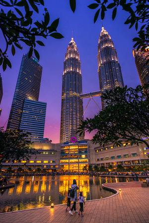 Tourists walking at Petronas Towers, Kuala Lumpur at dusk. It is the tallest twin towers in world.