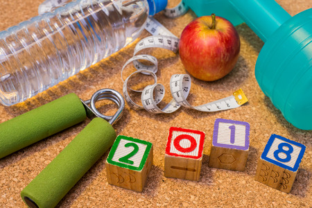 Lay Flat - Happy New Year 2018. Fitness & Healthy Eating Concept. Dumbell, Fresh Apple, Mineral Water, Measuring Tape, Hand Grip