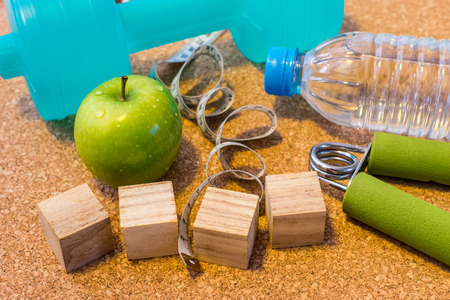Lay Flat - Dumbbell, Fresh Apple, Measuring Tape, Mineral Water & Blank Wooden Cubes, customizable for New Year. Fitness & Healthy Eating Concept