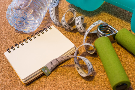 Lay Flat - Dumbbell,  Measuring Tape, Mineral Water & Blank Notebook for Motivational QuotesWords - Fitness Concept