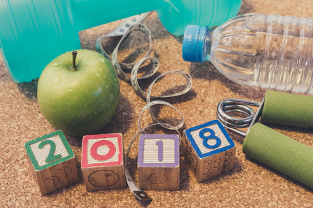 Lay Flat - Happy New Year 2018. Fitness & Healthy Eating Concept. Dumbbell, Fresh Apple, Mineral Water, Measuring Tape, Hand Grip