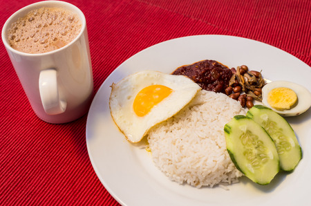 frothy: Malaysian Food - Nasi Lemak and Frothy Teh Tarik on a red background. Both dishes are unofficially the national breakfast dish of Malaysia. Teh tarik is basically a Tea with Milk
