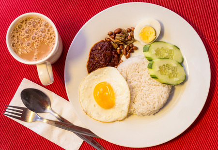 Malaysian Food - Nasi Lemak and Frothy Teh Tarik on a red background. Both dishes are unofficially the national breakfast dish of Malaysia. Teh tarik is basically a Tea with Milk