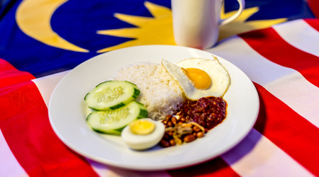 Malaysian Breakfast - Nasi Lemak and Teh Tarik on Malaysia Flag. Both dishes are unofficially the national breakfast dish of Malaysia. Shallow depth of field