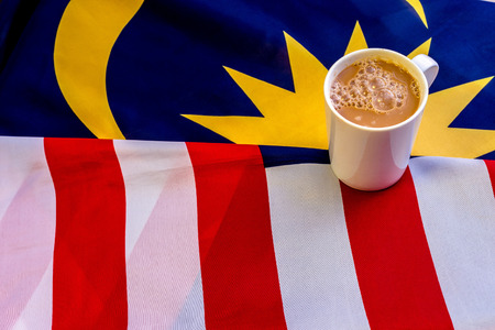 frothy: Malaysian Breakfast - Teh Tarik on Malaysia Flag. Teh Tarik is unofficially the national breakfast drink of Malaysia. It is a tea with milk Stock Photo