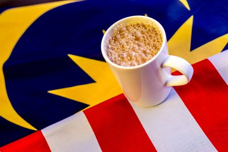 Malaysian Breakfast - Teh Tarik on Malaysia Flag. Teh Tarik is unofficially the national breakfast drink of Malaysia. It is a tea with milk Stock Photo