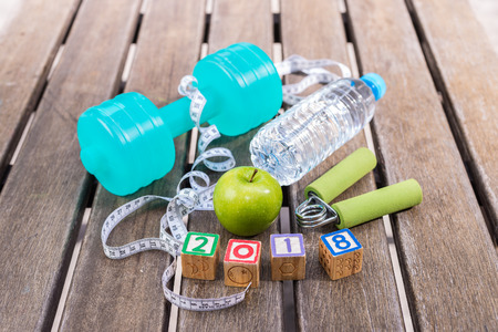 2018 Fitness Concept - Dumbbell, Measuring Tape, Mineral Water, Fresh Apple, Hand Grip & 2018 Wooden Blocks on a wooden table background. Motivation, goals and new year resolution concept Stock Photo