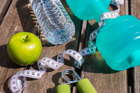 Fitness Concept - Dumbbell, Measuring Tape, Mineral Water, Fresh Apple, Hand Grip on a wooden table background. Motivation, goals and new year resolution concept. Shallow depth of field, selective focus Stock Photo