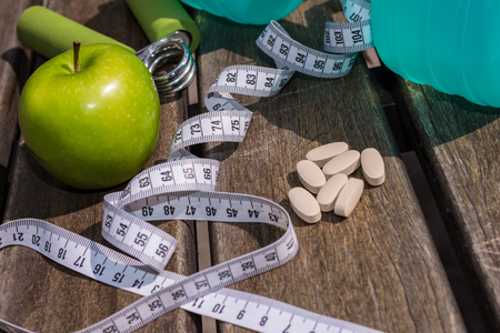 Fitness Concept - Dumbbell, Measuring Tape, Mineral Water, Fresh Apple, Hand Grip & vitaminssupplement tablets on a wooden table background. Motivation, goals and new year resolution concept