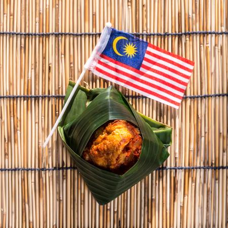 ナシゴレン Lemak はバナンの葉に包んでください。 マレーシア料理、マレーシアの国旗。マレーシアの非公式な国民の朝食料理。フィールドの浅い深