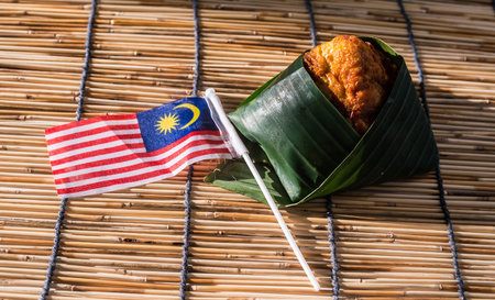 Nasi Lemak wrapped in banan leaf.  Malaysian Food and Malaysia Flag. The unofficial national breakfast dish of Malaysia. Shallow depth of field.