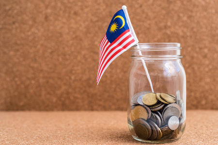 Malaysia Ringgit Coins & flag in a jar. Wood Background. Financial Concept. Shallow depth of field