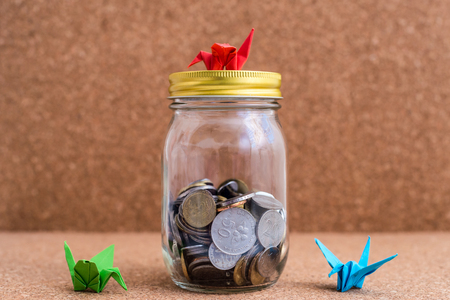 Malaysia Ringgit Coins in a jar with Colorful Origami Birds.  Wood Background. Financial Freedom Concept. Shallow depth of field