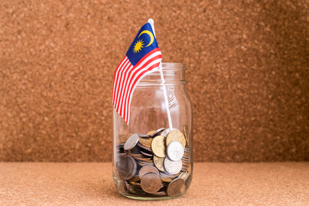 Finance concept - Malaysia Ringgit Coins in a jar with Malaysia Flag. Wood background. Shallow depth of field. Stock Photo - 83811007