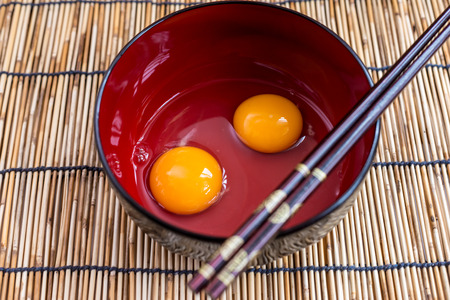Egg Yolk in a Red Rice Bowl with chopstick, shallow depth of field