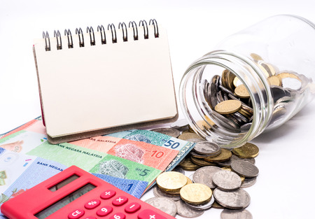 Jar of Malaysia Coins, Ringgit banknotes, red calculator and blank notepad for text. White background. Financial Concept.Shallow Depth of field