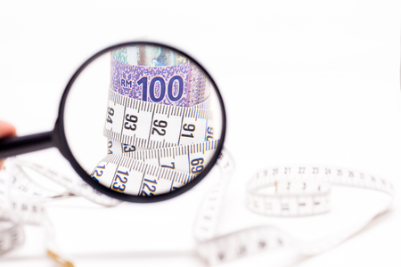 Magnifying Glass on Measuring Tape tightening Malaysia Ringgit Banknotes. Identifying Cost Saving concept. White Background. Shallow depth of field Stock Photo