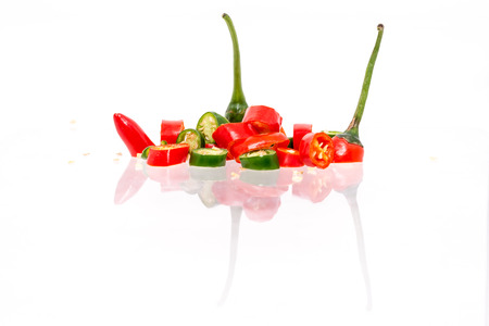Isolated White Background - Green and Red Chilis Reflected. Abstract reflection. Shallow depth of field