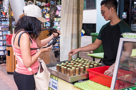 Malaysia, 2017 - Tourist photograping Putu Bambu, a Steamed Rice Dessert made by steaming rice flour filled with palm sugar with pandan leaf flavour and dried coconut flakes.