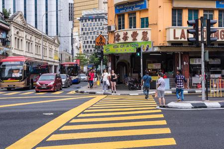 Maleisië, 2017 - Een oude dame probeert een weg over te steken met snelle passerende auto's. Maleisische automobilisten houden zich soms bezig met verkeersveiligheid.