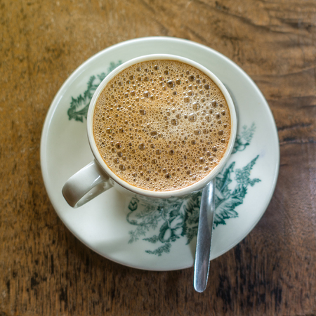kopitiam: Frothy Chinese ChaiCoffee with milk in vintage cup and saucer. Breakfast drink. Shallow depth of field