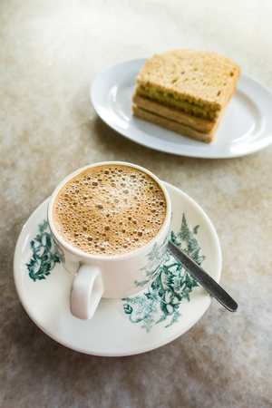 kopitiam: Frothy Chinese ChaiCoffee with milk in vintage cup and saucer. with toasted bread with margarine. Breakfast drink and food. Shallow depth of field Stock Photo