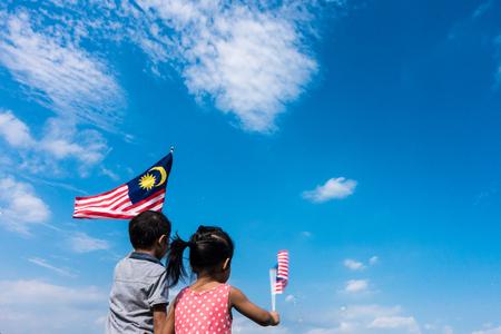 알 수없는 아이  형제 및 자매는 말레이시아 깃발을 흔들며. 독립 기념일 & Merdeka 개념. 푸른 하늘과 복사본 공간입니다.