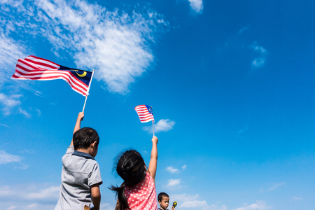 Unknown kids/brother and sister waving the Malaysia Flag. Independence Day & Merdeka Concept. Blue sky and copy space. 스톡 콘텐츠