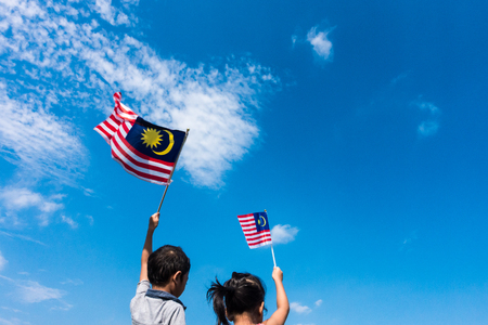 Unbekannte Kinder / Bruder und Schwester, die die Malaysia-Flagge wellenartig bewegen. Unabhängigkeitstag & Merdeka Konzept. Blauer Himmel und Kopie Raum. Standard-Bild - 84424473