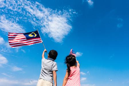Nieznane dzieci  brat i siostra macha flagą Malezji. Dzień Niepodległości i koncepcja Merdeki. Błękitne niebo i przestrzeni kopii.