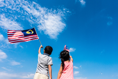 male and female: Unknown kidsbrother and sister waving the Malaysia Flag. Independence Day & Merdeka Concept. Blue sky and copy space. Stock Photo