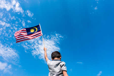 Unknown kid waving Malaysia Flag. Independence day and Merdeka Celebration. Blue sky and copy space. Фото со стока