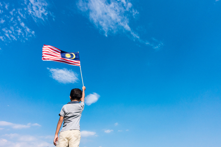 Unknown kid waving Malaysia Flag. Independence day and Merdeka Celebration. Blue sky and copy space. 版權商用圖片