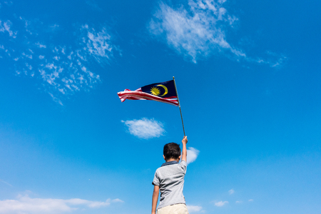 Unknown kid waving Malaysia Flag. Independence day and Merdeka Celebration. Blue sky and copy space. Stock Photo