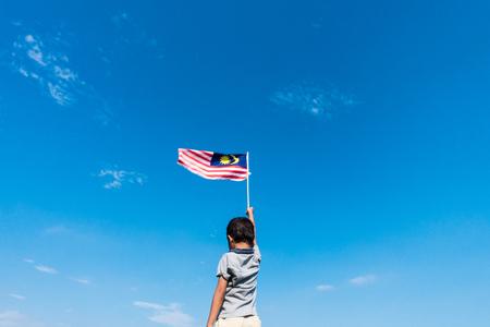 マレーシアの旗を振って未知の子供。独立記念日やムルデカお祝い。青い空とコピー スペース。 写真素材
