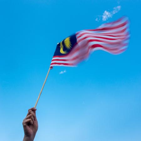 マレーシアの国旗を持っている手。風が吹いて、旗の動きぼやけ。青い空 写真素材