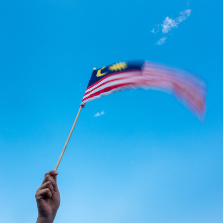 Hand Holding Malaysia Flag. Wind blowing, motion blur on flag. Blue Sky