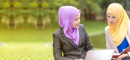Muslim Women Entrepreneurs having a business meeting by a lake with a laptop. 스톡 콘텐츠