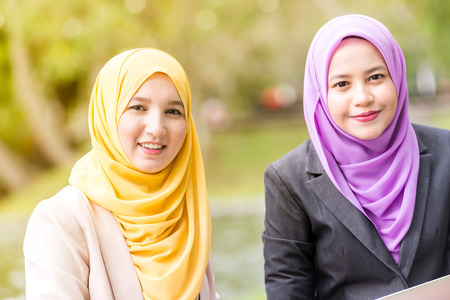 Muslim Women Entrepreneurs having a business meeting by a lake with a laptop. Looking at the camera Stock Photo