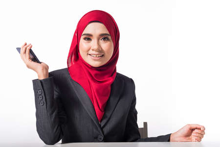 Muslim Female in Business attire isolated on white with her smartphone gadgets Reklamní fotografie